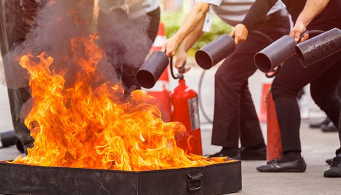 Les élèves manipulent les extincteurs pour éteindre un feu