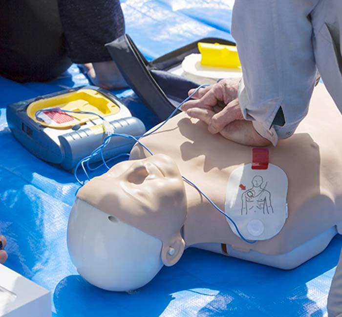 Pose d'un DSA sur une victime en réalisant des compressions thoracique à Villeurbanne