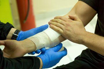 un soignant pose un pensement sur le bras d'un blessé