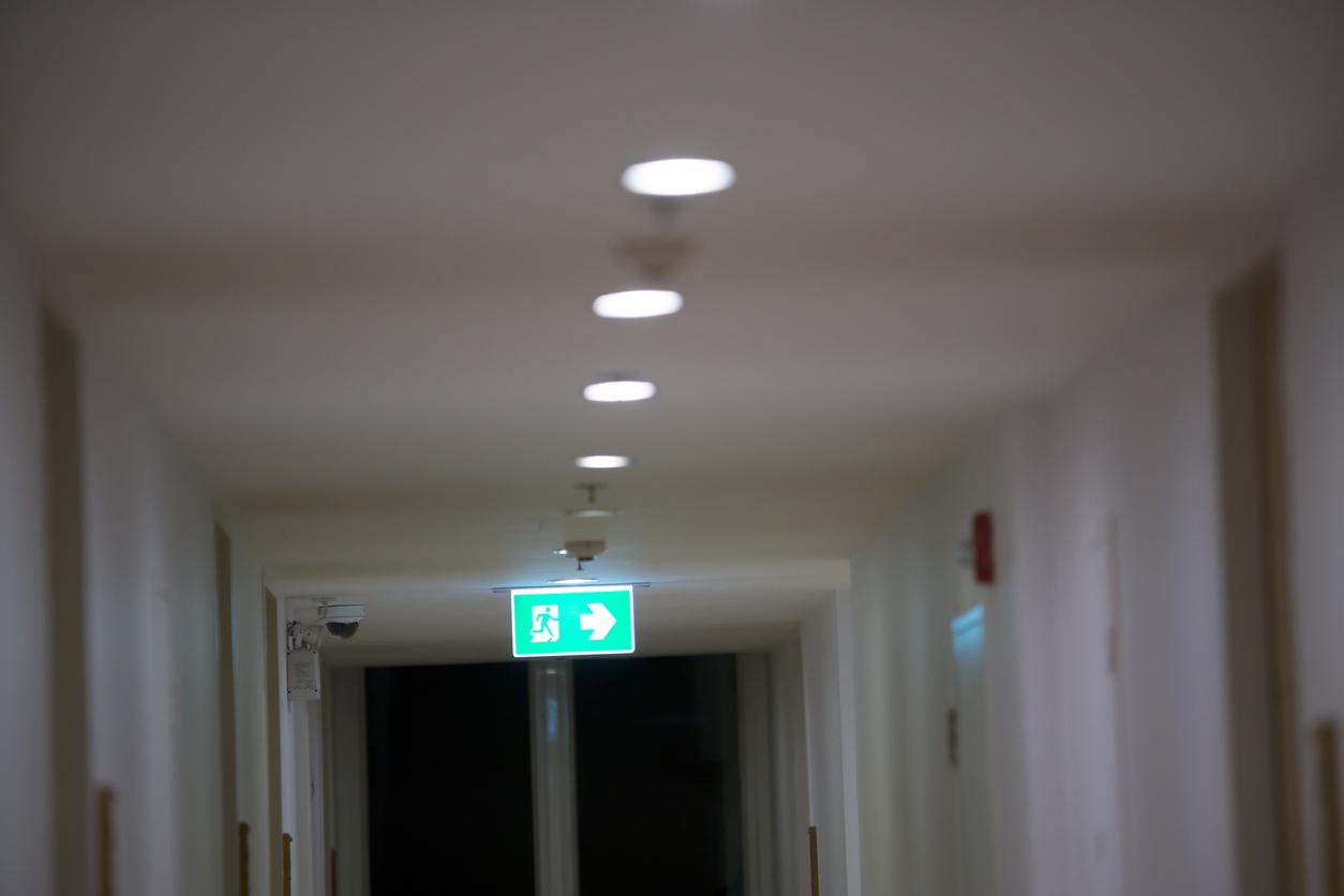 Un couloir d'un centre hospitalier éclairé par l'éclairage de sécurité pour donner le sens de l'évacuation