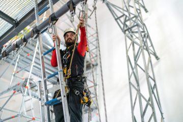 notre expert en travail en hauteur installe une ligne de vie provisoire en corde.